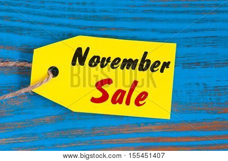 November Sale, price tag on blue wooden background.
