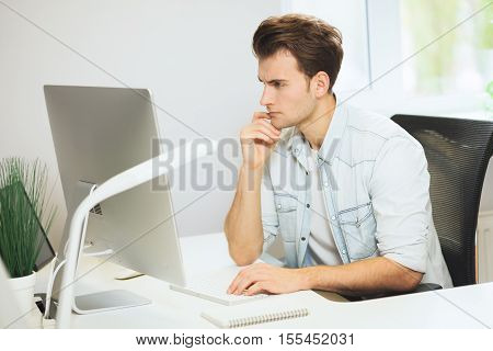 A young programmer is looking at the camera. The graphic designer is thinking about the future projects. The young guy is sitting at the computer in the office with the windows behind his back and holding up his head with his left hand