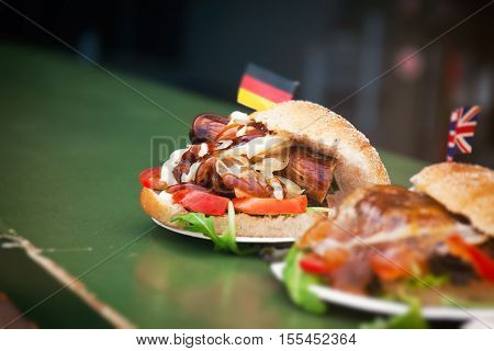Street food german burger with sausage vegetables ketchup and mayonnaise. Street food or unhealthy food concept.