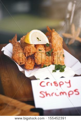 Tasty crispy fried shrimps with lemon and parsley with mayonnaise on a plate. Street food or unhealthy food concept