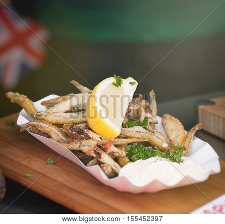 Tasty crispy fried fish with lemon and parsley with mayonnaise on a plate. Street food or unhealthy food concept