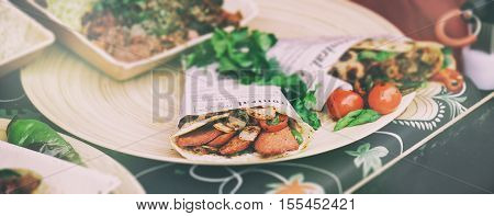 Street food sandwiches or tacos with grilled meat and vegetables. Street food or unhealthy concept horizontal vintage toned