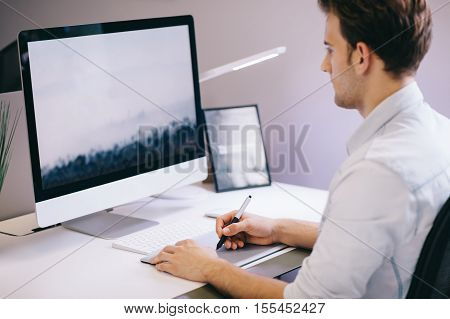 Young worker sitting in an office at the computer. Freelancer in a blue shirt. The designer sits in front of a window in the workplace. shot of screen. Space for your text or logo. Focus on screen