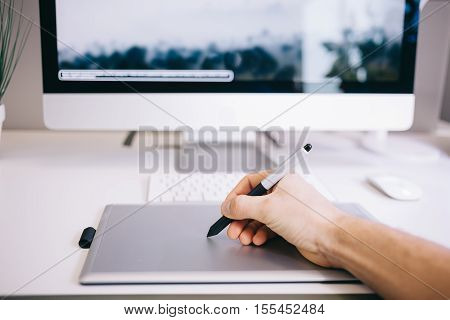 Young worker sitting in an office at the computer. Freelancer in a blue shirt. The designer sits in front of a window in the workplace. shot of screen. Space for your text or logo. Hand on shot
