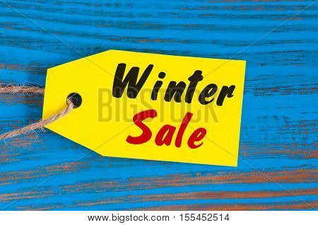 Winter Sale, price tag on blue wooden background.