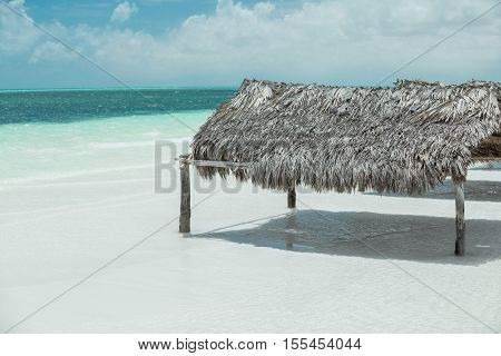 cozy comfortable beach shed on white sand tropical sunny beach against ocean and cloudy sky background