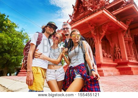 group of friends in front of red temple in thailand on koh samui