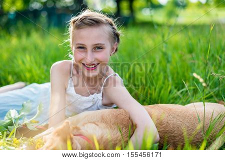 beautiful girl with a dog on the grass