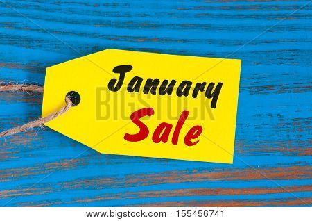 January Sale, price tag on blue wooden background.