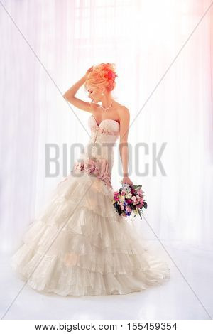 Beautiful fashion model. Sensual bride. Woman with wedding dress, hair and make up. Waiting for groom on background of window Blue eyes.  Beauty spring girl with bouquet of flowers in hands