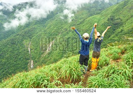Two friends stand together at the cliff,  raise their arms and seeing at the forest.