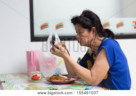 BANGKOK, THAILAND, SEPTEMBER 23, 2016 : Senior woman using smartphone at a street restaurant in Bangkok, Thailand