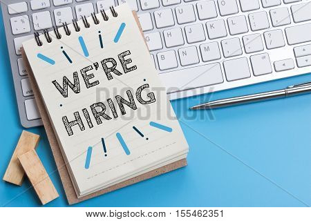 Word text We're hiring on white paper on office table / business concept