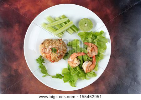 Fried rice with shrimp call Khao Pad Kong in Thai is popular asia food s with halved green lemonsliced cucumber and lettuce.