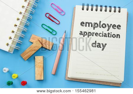 Text Employee appreciation day on white paper book and office supplies on blue desk / business concept
