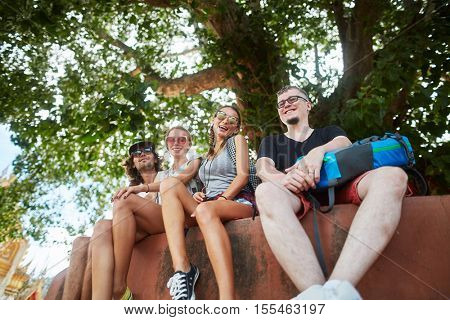 group of four tourists sitting under tree near temple in thailand