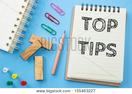 Text Top tips on white paper book and office supplies on blue desk / business concept