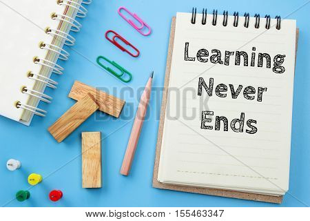 Text Learning never ends on white paper book and office supplies on blue desk / business concept