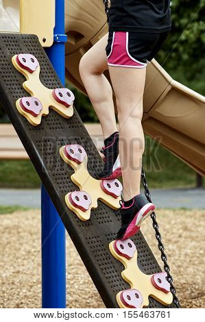 Legs Of Girl Climbing Playground Equipment