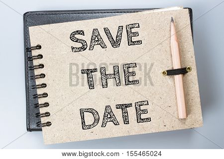Save the date, Text message on brown Notebook / business concept