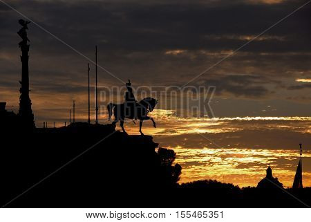 Sunset over Altar of Nation in the historic center of Rome with first king of Italy equestrian monument silhouette