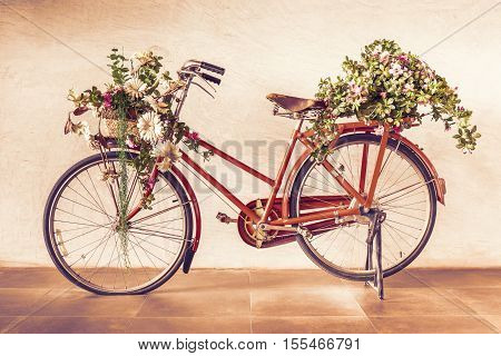 Vintage style of red bicycle with flower baskets parking against cement wall background.