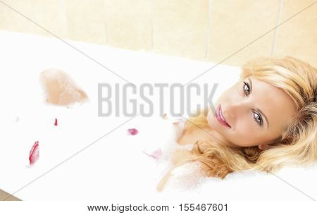 Passionate Sexy Blond Female Relaxing in Foamy Bath Covered with Flowery Petals. Horizontal Image Composition