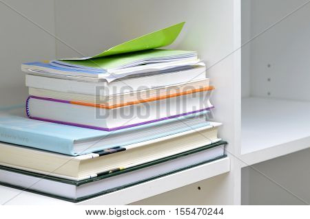 Pile of books and documents on bookshelf at business office.