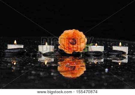 Spa still life with orange ranunculus and four candle on pebbles
