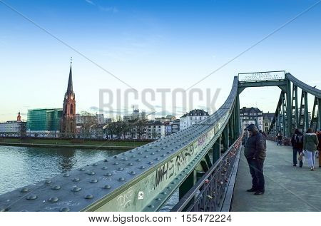 FRANKFURT, HESSE - February 12 : River view of The Eiserner Steg.The Eiserner Steg is a pedestrian bridge in Frankfurt am Main built in 1868. City skyline on February 12, 2014 in Frankfurt, Germany.