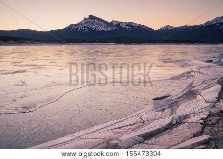 Landscape of frozen Abraham lake with a mountain in the background and ice sheets in the forground.