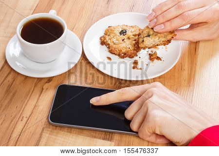 Hand Of Woman Using Mobile Phone, Oatmeal Cookies And Cup Of Coffee