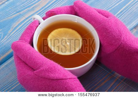 Hand Of Woman In Woolen Gloves Holding Cup Of Hot Tea On Table