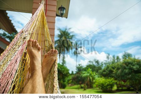 Relax in a hammock. A view of the man's feet resting in a hammock on the porch of a house or hotel.