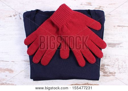 Pair Of Woolen Gloves And Sweater For Woman On Old Wooden Background