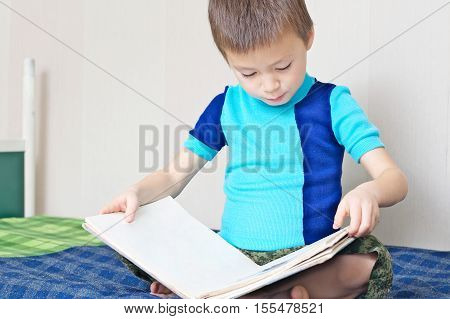 Little Boy reading book on bed oneself learning read