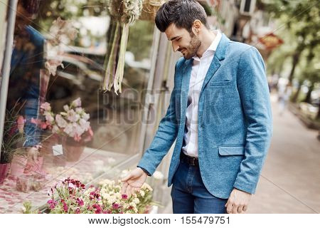 Young man buying flowers outdoors.