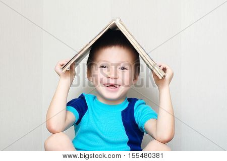 Happy smiling boy with book on head making roof