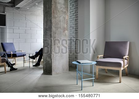 Zone in the office in a loft style with a concrete column and light walls. Near the column there are multi-colored armchairs with small round tables with a laptop. On the two armchairs sit people.