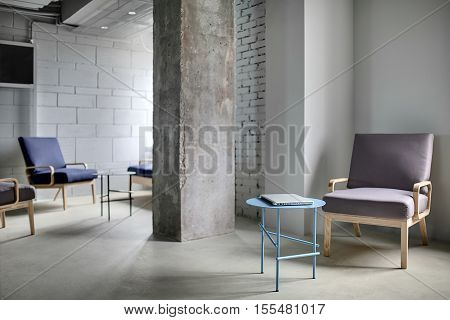 Work zone in the office in a loft style with a concrete column and light walls. Near the column there are multi-colored armchairs with wooden legs and small round metal tables with a laptop.