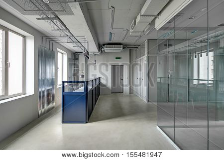 Blue metal reception rack with armchairs in a loft style office with gray walls. There is an entrance door and work zones with glass and mesh partitions. Table with chairs are reflected in the glass.