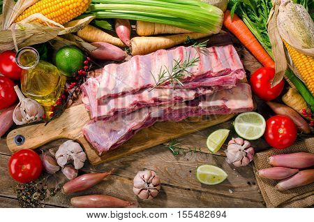 Raw Beef Ribs And Vegetables On  Wooden Background.