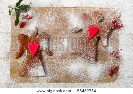 Two Christmas Gingerbread Angels On A Wooden Board.