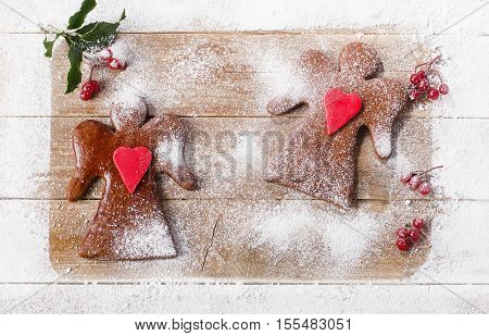 Two Christmas Gingerbread Angels On Wooden Board.