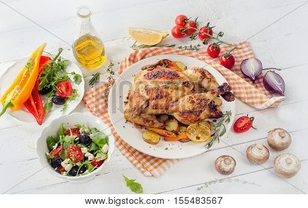 Roasted Chicken With Vegetables And Salad On A White Wooden Background.