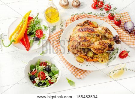 Whole Roasted Chicken With Vegetables And Salad On A White Wooden Background.