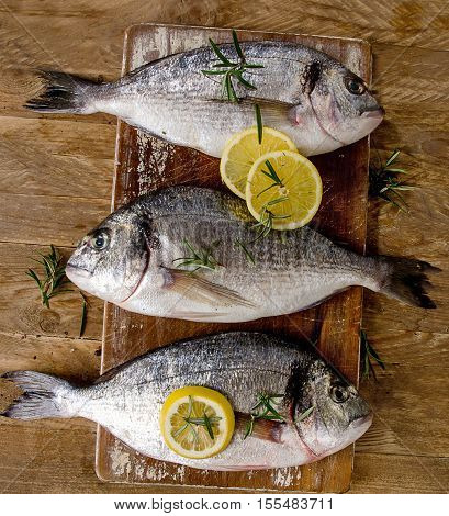 Fresh Fish With Lemon On A Wooden Background. Healthy Food Concept.