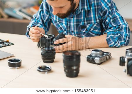 Maintenance of photo camera at workshop. Photographer cleaning photocamera light sensor. Professional photographing equipment care, technology, hobby concept