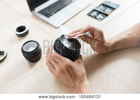 Camera lens cleaning with wet wipe, close-up. Photographer hands wiping lens on workplace . Professional photographing equipment care, technology, hobby concept