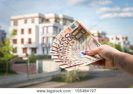 Property Buyer Holding Euro Banknotes - Real Estate Concept